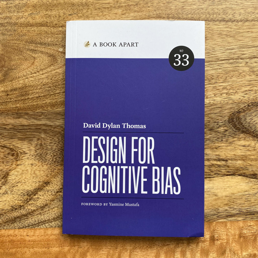 """David Dylan Thomas' book """"Design for Cognitive bias"""" on a mango wood table"""